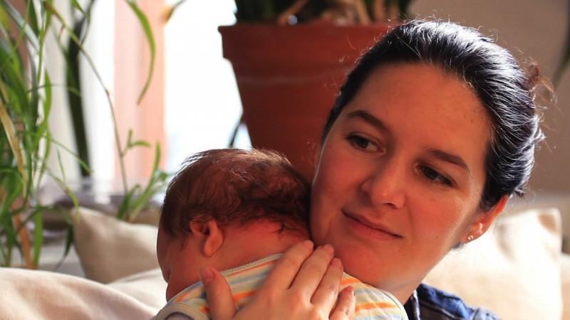Mutter hat ihr Baby auf der Schulter
